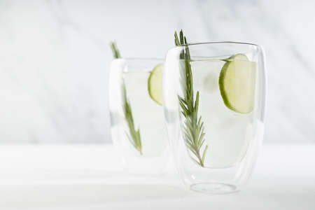 Healthy summer vitamin cold tonic drink with lime juice, ice, green rosemary twig in two glass mugs on white wood table and soft light marble wall. 免版税图像