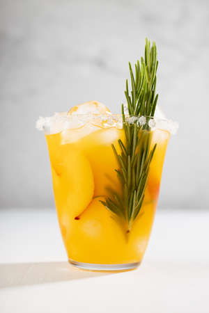 Fresh cold peach drink in glass with ice cubes, green rosemary, fruit slice, sugar rim in soft light white kitchen interior, vertical.