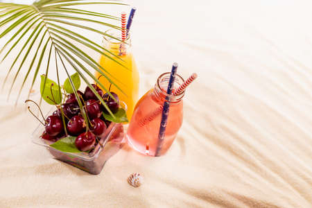 Tropical beach picnic with cold strawberry and orange cocktail in glass bottle, green palm leaf, fresh red cherry on yellow sand, copy space.