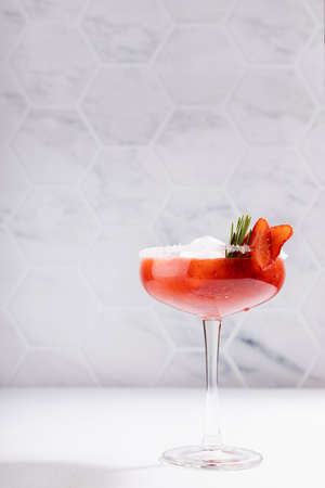 Fresh classic strawberry margarita cocktail with green rosemary twig, ice cube, fruit slices, sugar rim in modern white kitchen interior on wooden table in sunlight, vertical.