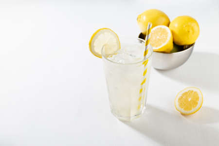 Fresh summer classic lemonade in glass with straw, ice, ingredients - lemons in silver bowl in soft light modern white kitchen interior with marble tile, sunlight. 免版税图像