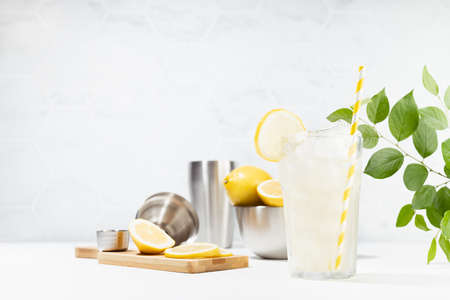 Healthy vitamin lemon drink cooking in soft light white kitchen with marble tile, green leaves in sunlight or outdoor - fresh natural lemonade with ice, ingredients on white wood table.