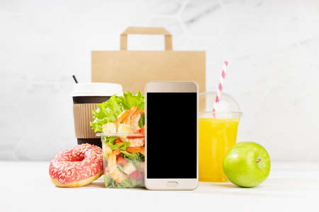 Lunch food set with coffee cup, orange juice, shrimp salad in plastic pack, apple, donut, packet, fruit, blank phone in white interior. Advertising for restaurant take away or delivery food service.