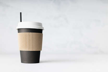 Coffee take away in black cardboard with cover, holder and straw on white wood board, marble tile wall, copy space. Template for branding identity or design.