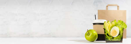 Wellness food banner - set of salad with lettuce, avocado, egg, cup of coffee, green apple, paper pack in light white interior. Concept advertising for restaurant take away or delivery food service.