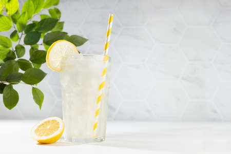 Cold juicy lemon cocktail in glass with straw, ice cubes, yellow slice with green branch in summer sunlight in soft light white kitchen interior with marble tile or garden. 免版税图像