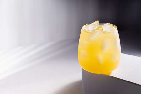 Cold orange fruit drink in glass on podium in elegant minimsl dark white wnd gray abstract interior with hard light and striped shadows.
