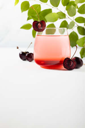 Cold cherry layered cocktail in misted glass with slice cherries, green fresh leaves in sunlight on soft light white wood table, marble wall, vertical.