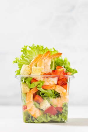 Organic vitamin meal - fresh sea food salad with shrimps, lettuce, red bell pepper, croutons in plastic box in white restaurant interior with marble tile wall, vertical. 免版税图像