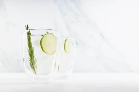 Fresh citrus infused homemade lemonade with ice cubes, lime slices, green rosemary twig in two mugs in soft light white kitchen interior in sunny day. 免版税图像
