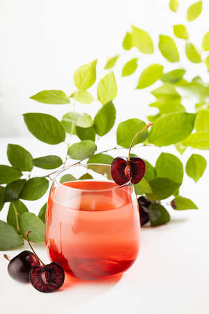 Summer refreshing healthy lemonade with cherry syrup, fruit slice in glossy glass with green leaves in golden sunlight in modern white restaurant interior with marble wall, vertical.