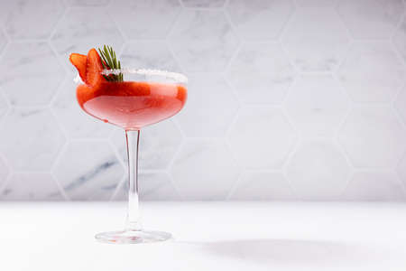 Cold fresh organic smoothies of ripe strawberry in high glass with sugar rim, green rosemary twig, fruit slices in soft light white interior bar with marble tile wall.