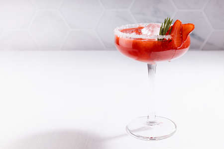 Cold summer strawberry alcohol cocktail margarita with frozen ice, green rosemary twig, berry slices, sugar rim in soft light white modern minimal interior in sunny day. 免版税图像