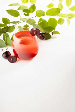 Cold fresh summer drink with cherry liqueur in glass with slice fruit, green leaves in sunlight in elegant sunny white interior on wood table or garden, top view, vertical. 免版税图像