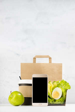 Healthy daily diet plan - set of cup of coffee, salad with avocado, egg, apple, paper pack in white interior, blank phone. Advertising for restaurant take away or delivery food service, online order.