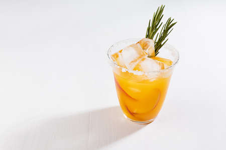 Fresh cold peach drink in glass with ice cubes, green rosemary, fruit slice, sugar rim on soft light white wooden table, top view.