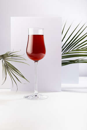 Red wine in exquisite glass in sunlight with striped shadows and green palm leaves in soft light white abstract interior with square, rectangle surfaces, vertical.