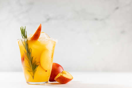 Healthy summer juice - peach cocktail with ice, rosemary twig, sugar rim, fruit slices in misted glass and ingredients in elegant white interior on soft light wood table.