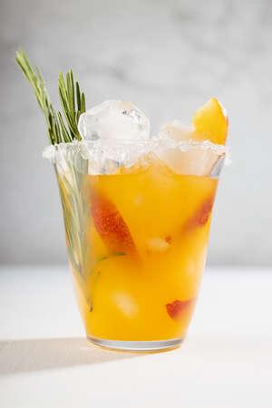 Homemade vitamin summer fresh orange peach lemonade with ice, green rosemary twig, sugar rim, fruit slices in misted glass on white wood table, soft light interior, vertical, closeup. 免版税图像