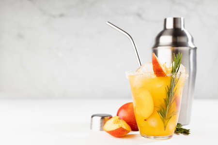 Cooking of homemade vitamin summer fresh orange peach lemonade with ice, green rosemary twig, sugar rim in misted glass, ingredients, silver straw, shaker on white wood table, soft light interior.