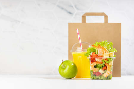 Healthy food set with fresh orange juice, tropical salad with shrimps, vegetables, apple in plastic packaging, packet in white interior. Concept advertising for restaurant take away, delivery service.