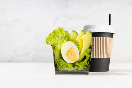 Organic lunch with cup of coffee, fresh green salad with avocado, egg in paper box in elegant white interior. Concept advertising for delivery and take away food service. Food cross section. 免版税图像