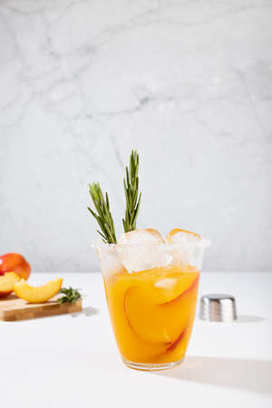 Cooking of fresh cold peach drink in glass with ice cubes, green rosemary, fruit slices, ingredients in soft light white kitchen interior, vertical. 免版税图像