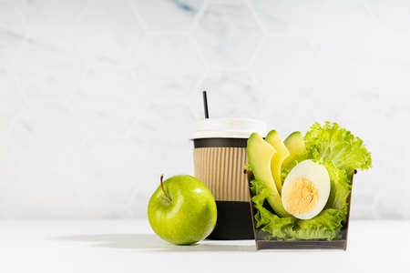 Healthy organic cuisine - set of salad with lettuce, avocado, egg, cup of coffee, green apple in white interior with marble tile wall. Advertising for delivery service or take away restaurant.