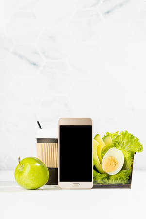 Organic cuisine - blank phone with set of green salad with lettuce, avocado, egg, cup of coffee, apple in white interior. Mockup advertising for delivery service, take away restaurant, online order. 免版税图像