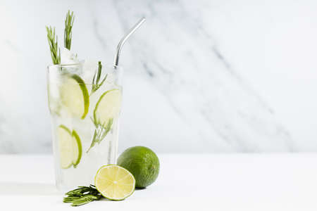 Summer refreshing organic citrus beverage with ice, lime slice, green rosemary twig, silver straw, ingredients in minimal soft light white bar interior in sunlight.