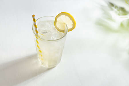 Lemon juice in soft light elegant white kitchen with green shadow of leaves in sunny day - lemonade in glass with straw, ice cubes, yellow lemon slice.