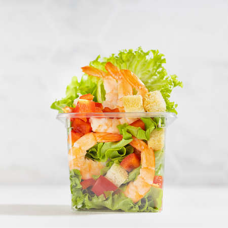 Healthy fresh summer salad with shrimps and vegetables in plastic box in soft light white kitchen interior with marble tile, closeup, square. Organic food take aw