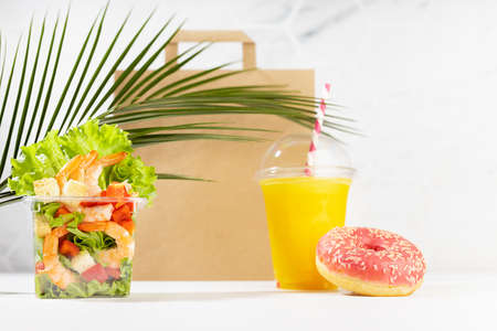 Healthy daily diet plan - set of orange juice, tropical salad with shrimps in plastic box, pink donut, packet in white interior, palm leaf. Advertising for restaurant take away, delivery food service.