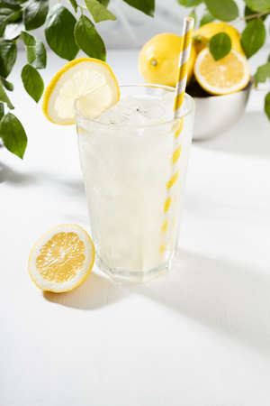 Detox fresh lemon juice of ripe lemons with ice in glass with ingredients in silver bowl, green branch in summer sunlight on white table, marble tile wall, vertical.