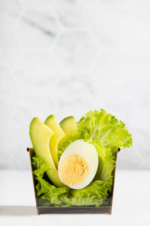 Healthy green salad take away with lettuce, avocado, egg in cardboard box on white wood table, marble tile wall. Concept food cut in half. Advertising for delivery restaurant, vertical. 免版税图像