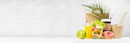 Summer take away food banner - set with drinks, coffee cup, orange juice, shrimp salad, noodles, donut, packet in white interior, palm leaf. Advertising for restaurant menu, delivery food service. 免版税图像