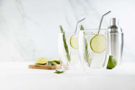 Refreshing mojito cocktail cooking with ice cubes, lime slices, green rosemary twig blended in silver shaker, two glass mugs with straws in elegant modern white interior on soft light wood table. 免版税图像