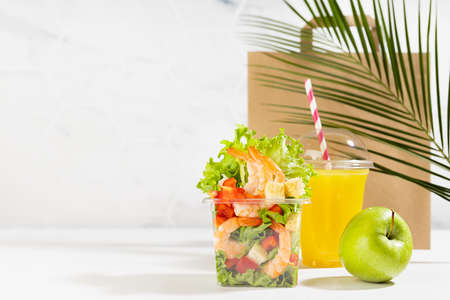 Summer lunch set with seafood salad with shrimps, orange juice, green apple in plastic pack, packet in white interior, palm leaf. Mockup for advertising for delivery service or take away restaurant.