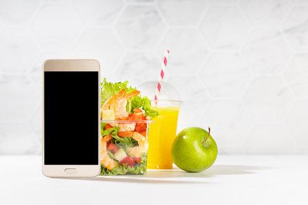 Healthy summer breakfast set of orange juice, shrimp salad, apple in plastic pack, blank phone in white kitchen interior. Mockup advertising for delivery service, take away restaurant, online order.