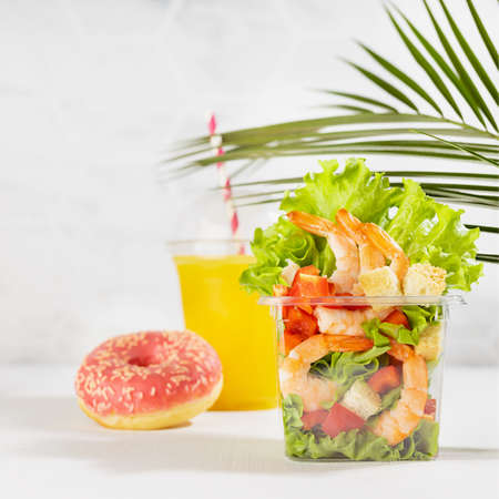 Bright summer lunch set with seafood salad with shrimps, red bell pepper, lettuce, croutons in plastic pack, fresh orange juice, pink donut in white interior with marble tile, palm leaf, square.