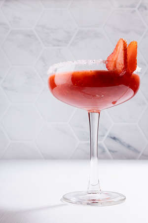 Summer fresh fruit strawberry cocktail of grinded red berry with sugar rim in glass goblen on white wood table with marble tile wall, vertical.