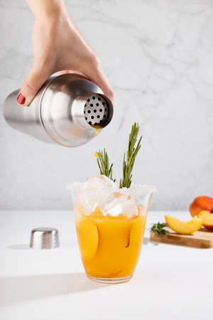 Cooking healthy summer peach juice - woman's hand pour cocktail pour of silver shaker in glass with ice, rosemary twig, sugar rim in elegant white interior on soft light wood table, vertical. 免版税图像