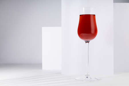 Red port wine in rich high glass in sunlight with shadow in modern minimal abstract white interior with geometric spaces.