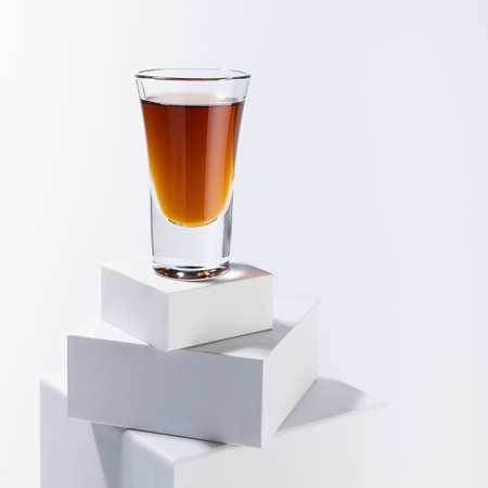 Golden scotch in shot glass in sunlight with shadows on white square podium with reflections in soft light abstract space in minimal modern style, square.