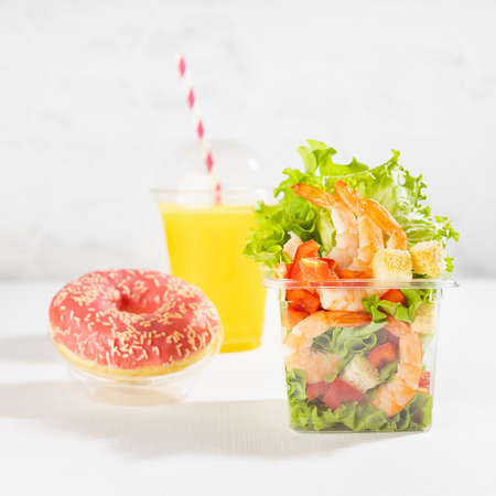 Healthy fresh summer breakfast take away - set of orange juice, salad with shrimps, red bell pepper, lettuce, croutons, pink donut in plastic package in white kitchen interior, square.