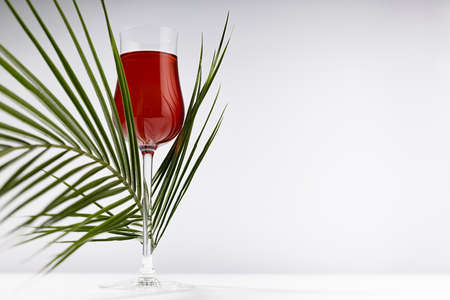 Red liquor in rich glass with curved summer bright green palm leaves as decoration in soft light white abstract interior on wood table. 免版税图像