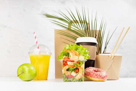 Summer take away food set with drinks, coffee cup, orange juice, shrimp salad, noodles, apple, donut, packet in white interior, palm leaf. Advertising for restaurant menu, delivery food service.