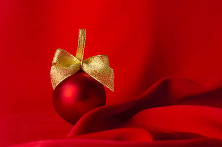 Rich christmas decoration - red ball with golden ribbon standing on saturated red silk background with elegant wave, copy space. Christmas background for design of poster, flyer, card, brochure.