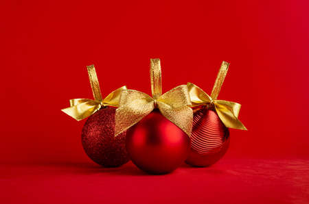 Three red glossy different christmas balls with gold shimmer bow on bright red background, copy space. Christmas background in modern minimal style for design of poster, flyer, card, brochure.