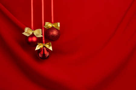 Rich red christmas background - shimmer balls with golden bows hang on ribbons in row on saturated silky wavy backdrop, copy space. New year background for design of poster, flyer, card, brochure. 免版税图像